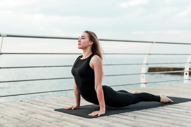 Sportive woman doing yoga asana on the sea in the morning Premium Photo