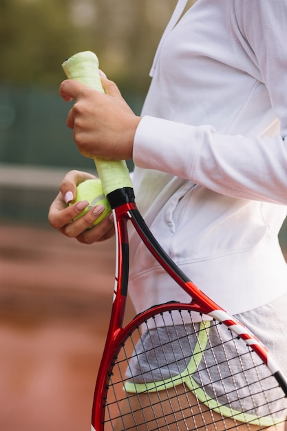 Sportive woman holding a tennis racket with the ball Free Photo