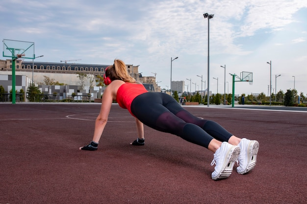 Sportive woman in stretch outfits doing warm up activity on the land. Free Photo