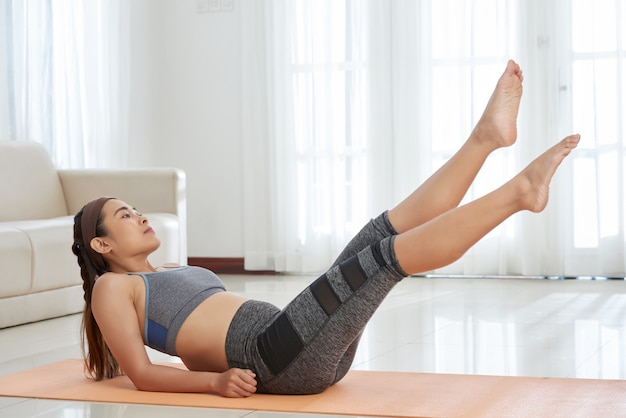 Sportive woman training abs on mat Free Photo
