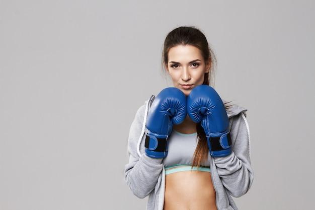 白のトレーニング青いボックス手袋を身に着けている陽気な女性。 無料写真