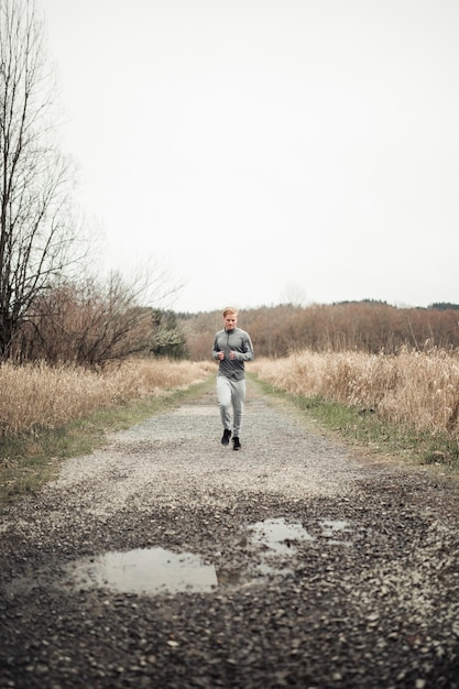Sportive young male running on dirt road in the field Free Photo