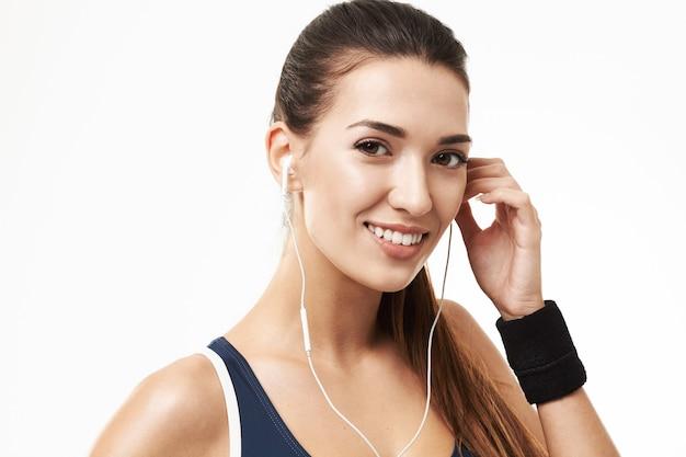 Жизнерадостная sportive женщина фитнеса в наушниках усмехаясь на белизне. Бесплатные Фотографии