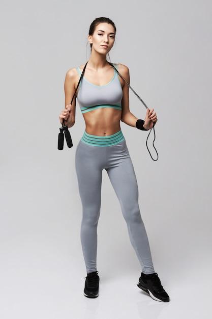 Женщина молодого фитнеса sportive представляя держащ скача веревочку на белизне. Бесплатные Фотографии
