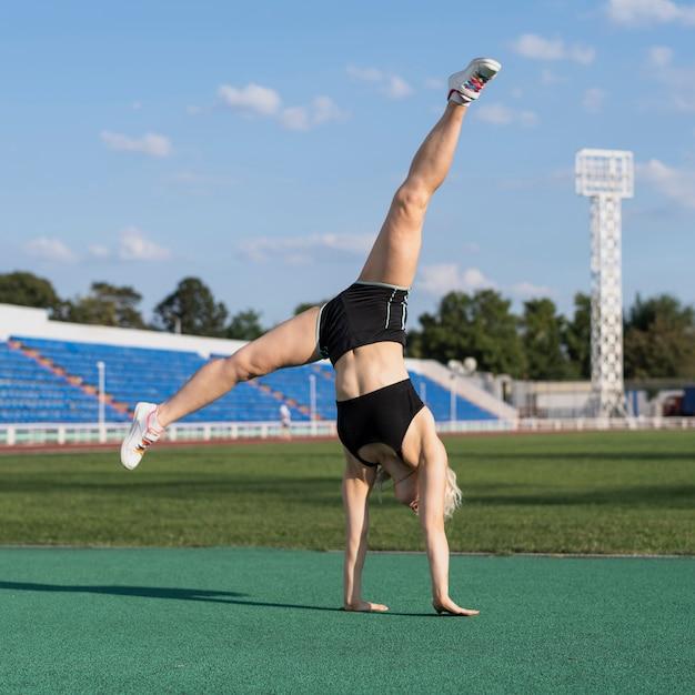Sportive женщина делает позу колеса Бесплатные Фотографии