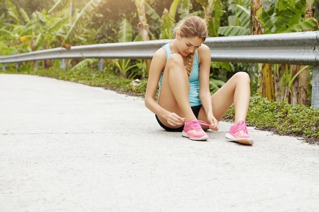 スポーツと健康的なライフスタイルのコンセプト。屋外のジョギング運動中にピンクのスニーカーをひもで締める道に座っているスポーティな少女。 無料写真