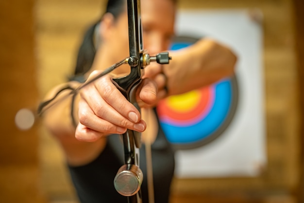 Sports archery woman at the shooting range, competition for the most points to win the cup Premium Photo