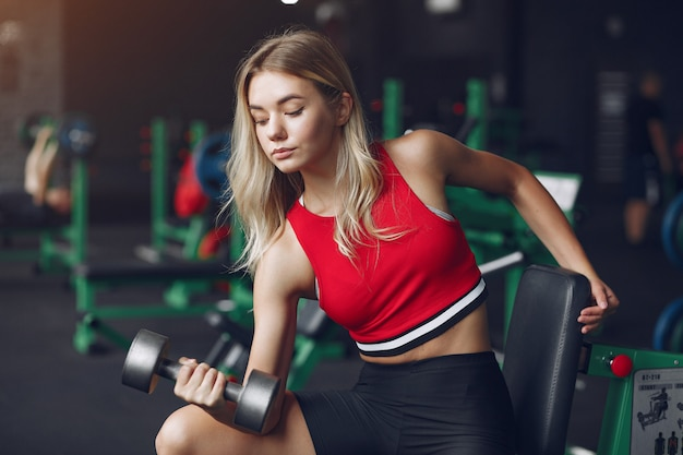 Sports blonde in a sportswear training in a gym Free Photo
