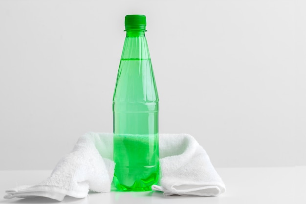 Sports bottle with towel on light Premium Photo