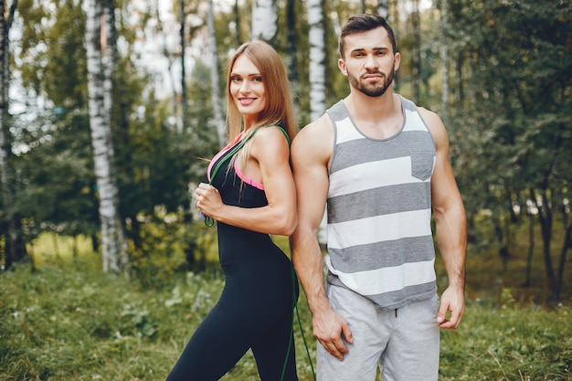 Sports couple in a morning summer park Free Photo