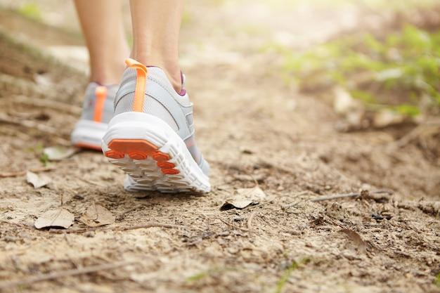 Sport, fitness e concetto di stile di vita sano. blocca l'azione ravvicinata del corridore femminile che cammina o fa jogging sul sentiero. giovane donna atletica che indossa scarpe da corsa durante le escursioni nel parco. Foto Gratuite
