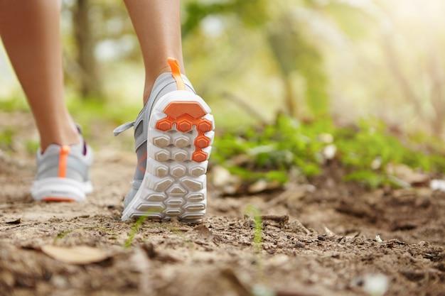 Sport, fitness, natura e concetto di stile di vita sano. giovane corridore femminile che indossa scarpe da ginnastica o scarpe da corsa durante le escursioni o fare jogging nel parco in giornata di sole. Foto Gratuite