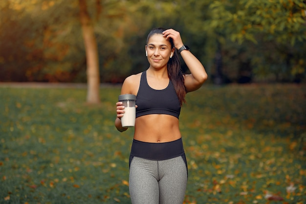 Sports girl in a black top training in a autumn park Free Photo