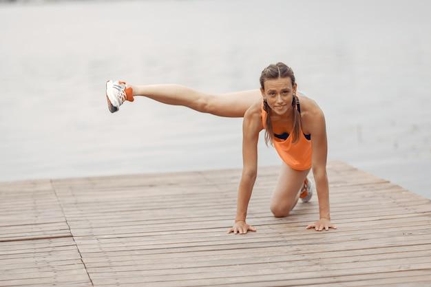 Ragazza di sport sull'acqua. donna in un parco estivo. signora in abiti sportivi arancioni. Foto Gratuite