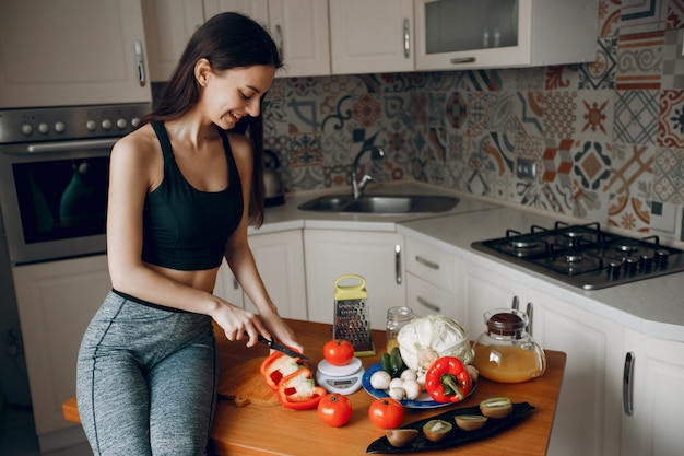 Sports girl in a kitchen with vegetables Free Photo