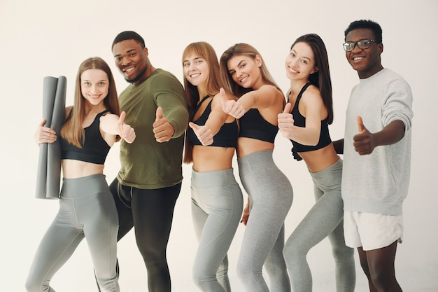 Sports group standing on a white wall Free Photo