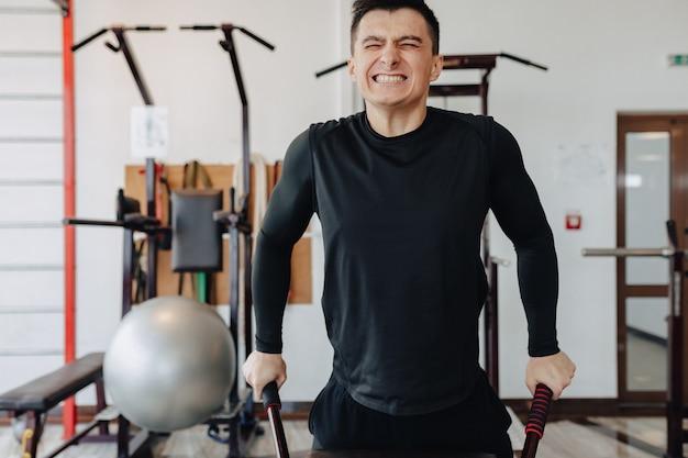 Спортивный парень сжимает на штангах, упражнения на грудных мышцах. здоровый образ жизни. Бесплатные Фотографии