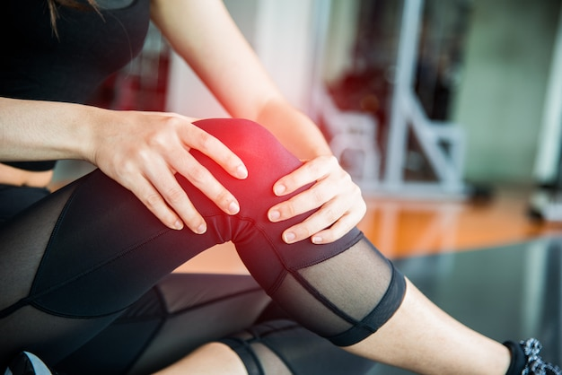 Sports injury at knee in fitness training gym. Training and medical concept Premium Photo
