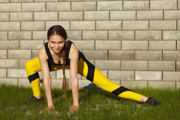 Sport, estate, fitness e concetto di stile di vita attivo sano. giovane donna caucasica atletica alla moda con i muscoli di allungamento della treccia lunga sull'erba verde, facendo affondi laterali, avendo sguardo sicuro Foto Gratuite