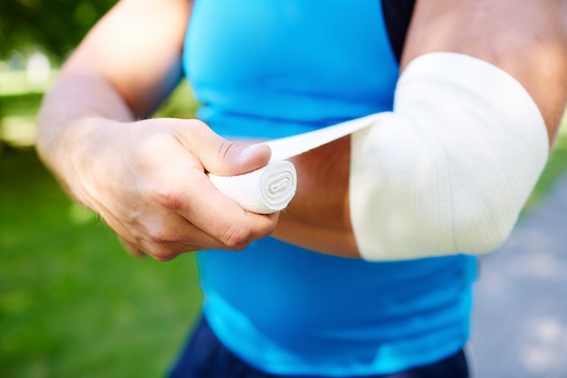 Sportsman bandaging the elbow Free Photo