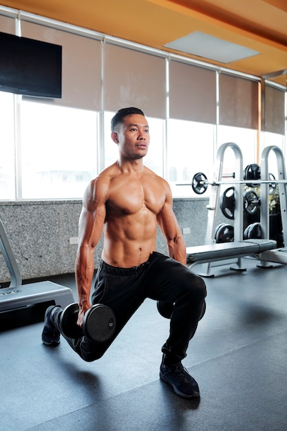 Sportsman concentrated on doing lunges Premium Photo