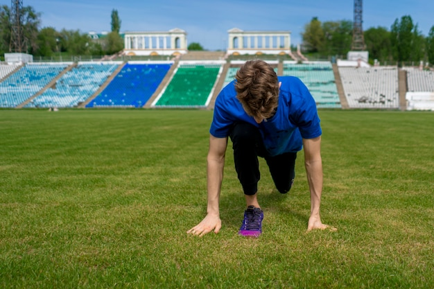 Sportsman doing stretching exercise on the stadium before summer practices Premium Photo