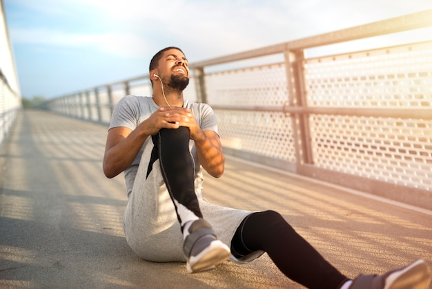 Sportsman having knee injury problem during running training Free Photo
