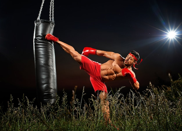Sportsman is training on a black night background Premium Photo