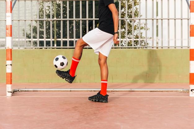Sportsman kicking football at stadium Free Photo