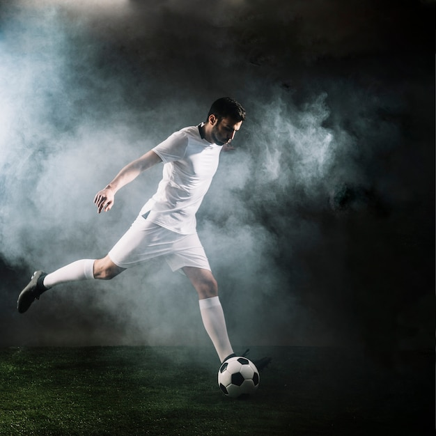 Sportsman kicking soccer ball in smoke Free Photo