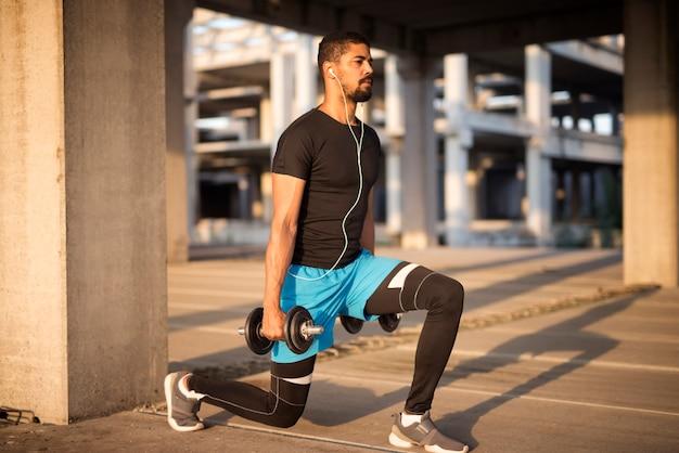 Sportivo che ascolta musica e si allena con i pesi Foto Gratuite