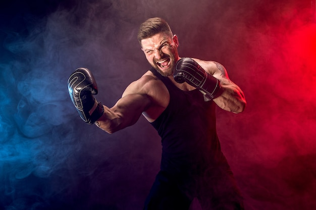 Sportsman muay thai boxer fighting on black wall with smoke. Premium Photo