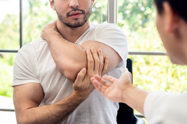 Sportsman patient consulting with doctor about muscule pain in clinic Premium Photo