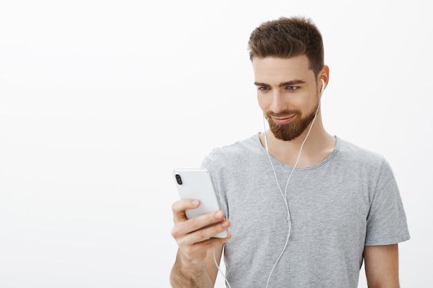 正しいトラックスタートの練習を検索するスポーツマン。携帯電話の画面を見て喜びとにやにや笑うスマートフォンを保持しているイヤホンで音楽を聴く青い目を持つ自信を持って、ハンサムなカリスマ的なひげを生やした男 無料写真