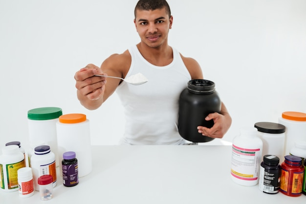 Sportsman standing over white wall holding vitamins Free Photo