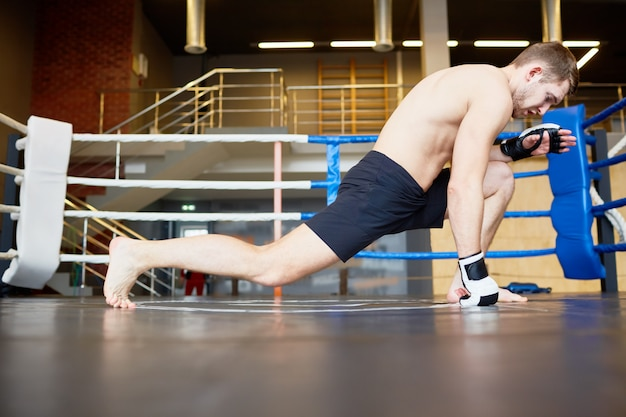 Sportsman stretching legs in boxing ring Free Photo