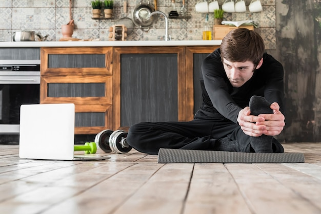 Sportsman stretching up on exercise mat Free Photo