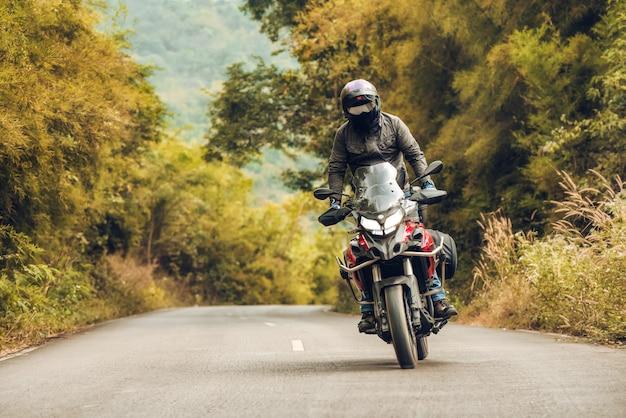 日没時に田舎でsportsterバイクに乗る男 Premium写真