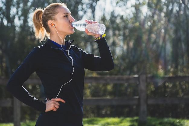 Sportswoman drinking water outdoors Free Photo