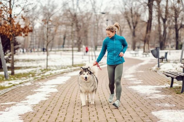 추운 겨울 날 공원에서 그녀의 강아지와 함께 실행하는 Sportswoman. 애완 동물, 겨울 피트니스, 러너, 공생 프리미엄 사진