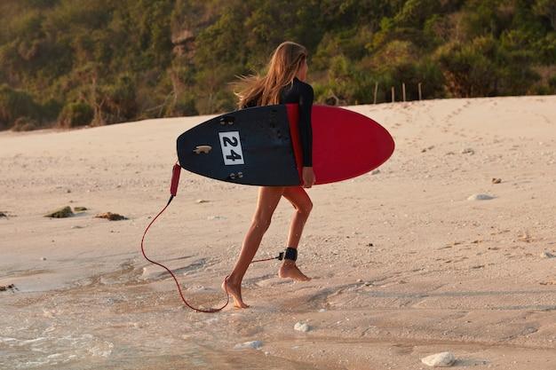 Спортсменка довольна хорошими погодными условиями меховым серфингом, бегает по мокрому песку у океана Бесплатные Фотографии
