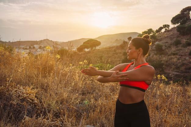 Спортсменка растягивается с красивым пейзажем Бесплатные Фотографии
