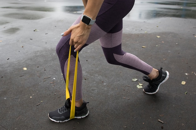 Спортсменка тренируется с желтой эластичной веревкой на спортивных площадках в парке Premium Фотографии