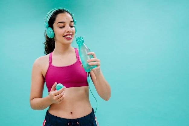 Sportswoman with earphones drinking water Free Photo