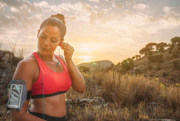 Sportswoman con auricolari nella natura Foto Gratuite