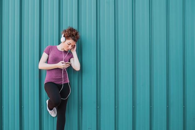 Sportswoman with headphones and phone on street Free Photo