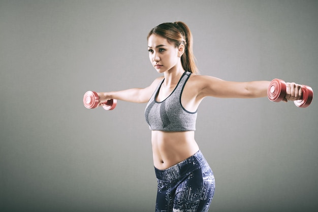 Sporty asian girl doing lateral raise with dumbbells Free Photo