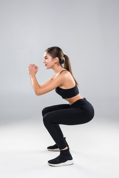 白い壁に分離されたジムで腹筋を行うしゃがむスポーティな運動女性 無料写真