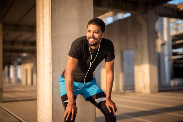 Maschio attraente sportivo che ascolta la musica e che sorride sulla formazione Foto Gratuite