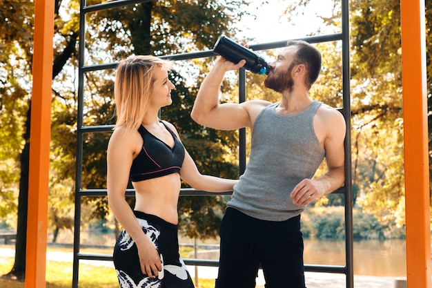 Sporty caucasian couple is resting after workout training in a park at autumn day. man drinking water from a black bottle. Premium Photo